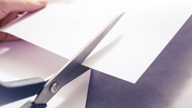 A Pair Of Scissors Cutting White Paper, Held By Female Hands