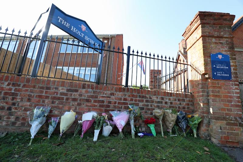 Flowers placed at the entrance to the Holt School, Wokingham, Berskhire, in memory of teacher James Furlong, a victim of the terrorist attack in Forbury Gardens, Reading, on Saturday in which three people died.
