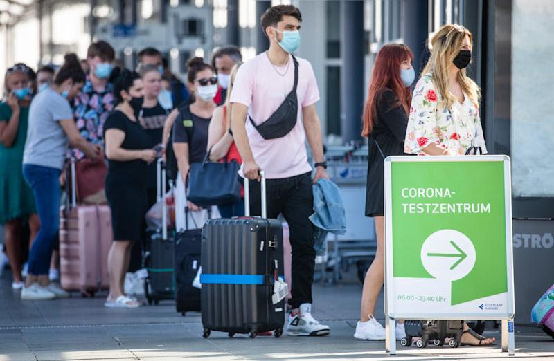 16 August 2020, Baden-Wuerttemberg, Stuttgart: Travel returnees, mainly from Spain, stand in front of the corona test centre at Stuttgart Airport wearing face masks. In view of the increased risk of infection, the German government has classified almost all of Spain, including Majorca, as a risk area. The classification means that returning holidaymakers are required to test for the new corona virus. Photo: Christoph Schmidt/dpa (Photo by Christoph Schmidt/picture alliance via Getty Images)