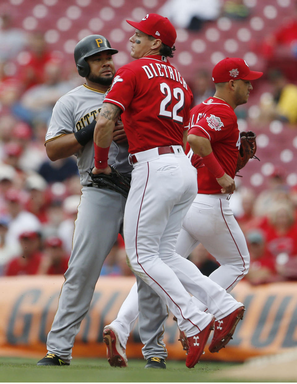 Pittsburgh Pirates Melky Cabrera, left, is tagged out in a rundown by Cincinnati Reds first baseman Derek Dietrich (22) on a ball off the bat of Colin Moran during the fourth inning of a baseball game, Wednesday, May 29, 2019, in Cincinnati. (AP Photo/Gary Landers)