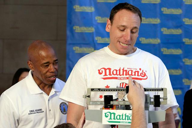 <p>Current men's champion Joey Chestnut, right, of San Jose, Calif., watches the scale during his weigh-in for the 2017 Nathan's Hot Dog Eating Contest, in Brooklyn Borough Hall, in New York, Monday, July 3, 2017. Looking on with him is Brooklyn Borough President Eric Adams. Chestnut weighed-in at 221.5 pounds. (AP Photo/Richard Drew) </p>