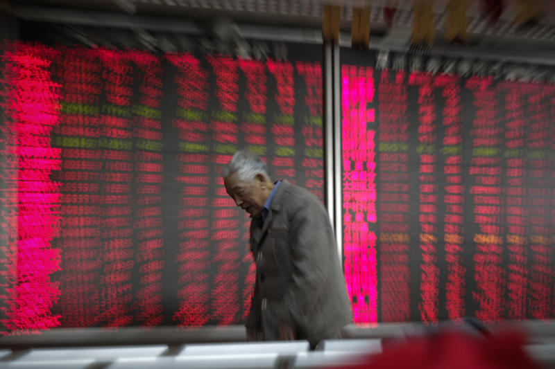A man walks by an electronic board displaying stock prices at a brokerage house in Beijing, Wednesday, Jan. 9, 2019. Shares extended gains in Asia on hopes for progress in resolving the tariffs battle between the U.S. and China as talks appeared to have been extended in Beijing. (AP Photo/Andy Wong)