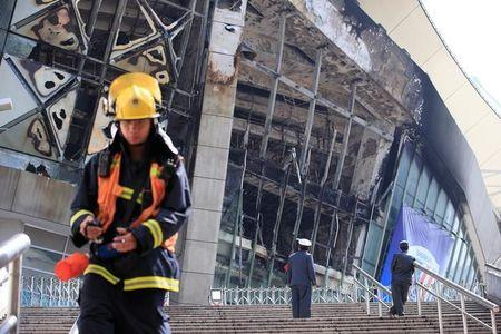 Rescue workers stand outside the site where a fire broke out at the Shanghai Hongkou soccer stadium in Shanghai
