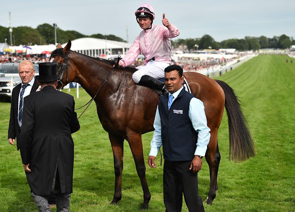 Jockey Seamie Heffernan poses for a photograph after riding Anthony Van Dyck to victory in the Derby Stakes.