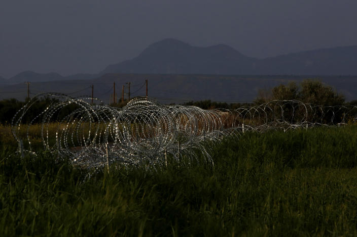 """Razor wire is seen along the southern side of a U.N buffer zone that cuts across the ethnically divided Cyprus, near village of Astromeritis, Tuesday, March 9, 2021. The government of ethnically split Cyprus has come under fire over a decision to lay razor wire along a section of a U.N. controlled buffer zone it said is needed to stem migrant inflows from the island's breakaway north, with critics charging that the """"ineffective"""" scheme only feeds partitionist perceptions amid a renewed push resume dormant peace talks. (AP Photo/Petros Karadjias)"""