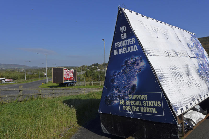 "In this photo taken on Wednesday, Oct. 10, 2018, a sign in a parking lot of a cemetery reads: ""No EU border in Ireland"" near Carrickcarnan, Ireland, just next to the Jonesborough Parish church in Northern Ireland. The land around the small town of Carrickcarnan, Ireland is the kind of place where Britain's plan to leave the European Union walks right into a wall - an invisible one that is proving insanely difficult to overcome. Somehow, a border of sorts will have to be drawn between Northern Ireland, which is part of the United Kingdom, and EU member country Ireland to allow customs control over goods, produce and livestock once the U.K. has left the bloc. (AP Photo/Lorne Cook)"