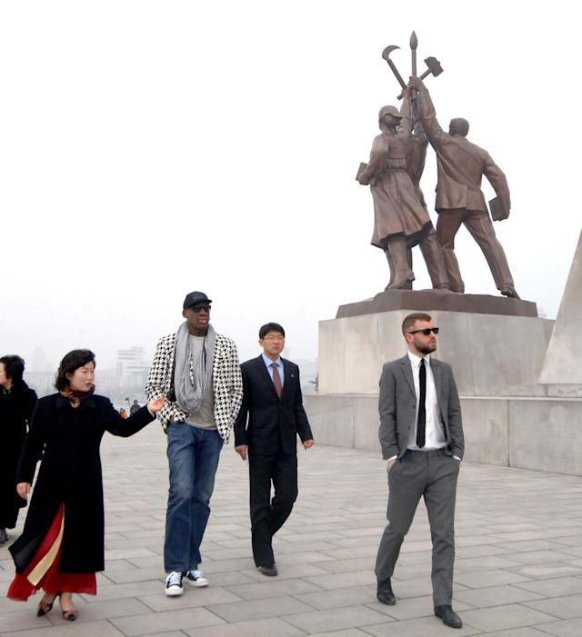 "In this image released by the Korean Central News Agency (KCNA) and distributed by the Korea News Service, former NBA star Dennis Rodman, third right, walks by the base of the Tower of the Juche Idea in Pyongyang in North Korea Friday, March 1, 2013. Ending his unexpected round of basketball diplomacy in North Korea on Friday, ex-NBA star Rodman called leader Kim Jong Un an ""awesome guy"" and said his father and grandfather were ""great leaders."" (AP Photo/KCNA via KNS) JAPAN OUT UNTIL 14 DAYS AFTER THE DAY OF TRANSMISSION"