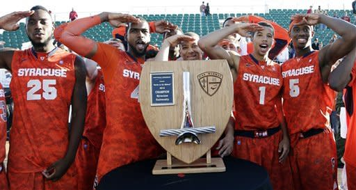 From left, Syracuse's Rakeem Christmas, Nolan Hart, Brandon Triche, Michael Carter-Williams and C.J. Fair salute in honor of Veterans Day as they pose for photos with the trophy after defeating San Diego State 62-49 in an NCAA college basketball game on the deck of the USS Midway, Sunday, Nov. 11, 2012, in San Diego. (AP Photo/Gregory Bull)