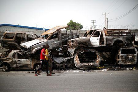 Two men walk past burnt cars piled in a street of Port-au-Prince, Haiti, July 12, 2018. REUTERS/Andres Martinez Casares