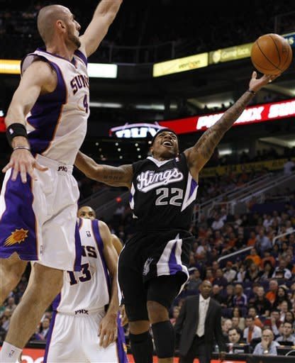 Sacramento Kings guard Isaiah Thomas, right, shoots and scores against Phoenix Suns center Marcin Gortat of Poland, in the second quarter during an NBA basketball game on Sunday, March 4, 2012, in Phoenix, Ariz. (AP Photos/Rick Scuteri)