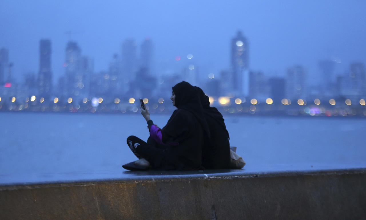 An Indian Muslim woman checks her phone as she sits with another on the Arabian sea coast in Mumbai, India, Tuesday, July 30, 2019. Indian lawmakers on Tuesday approved a bill to end the Muslim practice of instant divorce two years after the Supreme Court ruled that it violated the constitutional rights of Muslim women. (AP Photo/Rajanish Kakade)