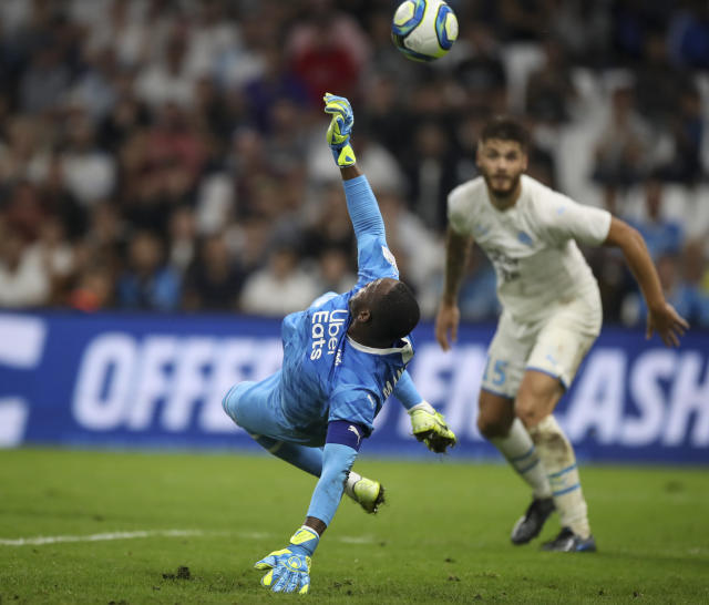 Marseille's goalkeeper Steve Mandanda saves a goal during the second half of the French League One soccer match between Marseille and Rennes at the Velodrome stadium in Marseille, southern France, Sunday, Sept. 29, 2019. (AP Photo/Daniel Cole)