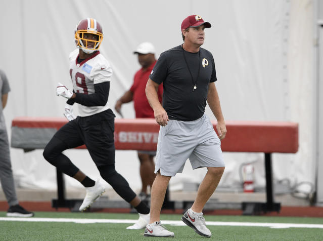 In this June 13, 2018, photo, Washington Redskins coach Jay Gruden, right, watches the NFL football team's practice in Ashburn, Va. If their fathers time in college football at Notre Dame and Indiana or his work in the NFL swayed their career choices, Jay and Jon Gruden credit their mother, Kathy, with instilling other key qualities. (AP Photo/Nick Wass)