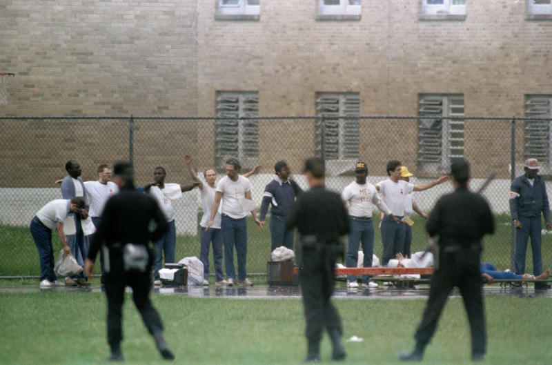 FILE - This April 21, 1993 file photo shows inmates raising their hands in surrender as armed guards watch on the recreation yard of the Southern Ohio Correctional Facility in Lucasville, Ohio. In the 20 years since the nation's longest deadly prison riot broke out in Lucasville, no interviews have been granted with the five men sentenced to death in the killing of a guard. Yet time has brought new evidence and insights that will dominate events marking the 20th anniversary of the 11-day siege of April 1993. (AP Photo/Lennox McLendon, File)