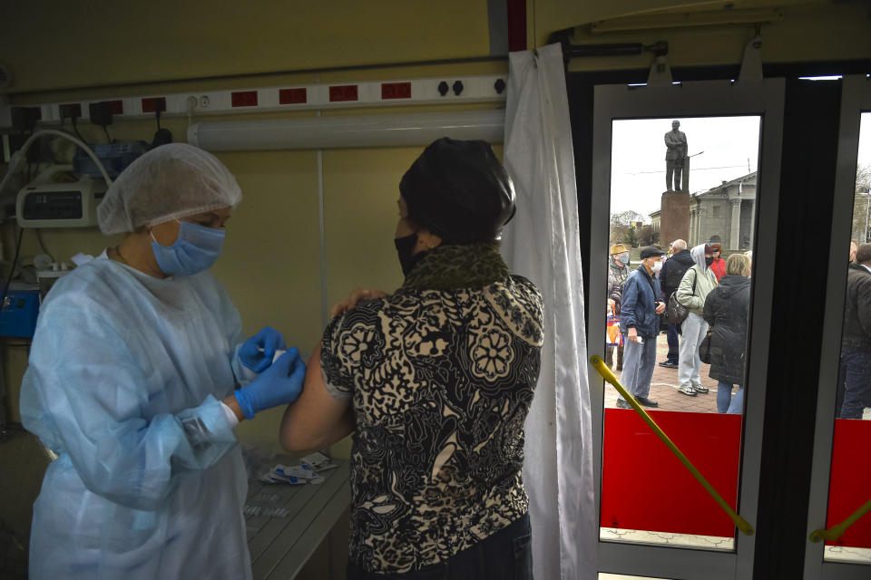 A Russian medical worker administers a shot of Russia's Sputnik V coronavirus vaccine for a woman as people wearing face masks to protect against coronavirus queue to get a shot of Russia's Sputnik V coronavirus vaccine in a mobile vaccination center with a statue of Vladimir Lenin in the background in Simferopol, Crimea, Tuesday, April 13, 2021. Russia has boasted about being the first country in the world to authorize a coronavirus vaccine and rushed to roll it out earlier than other countries, even as large-scale testing necessary to ensure its safety and effectiveness was still ongoing. (AP Photo/Alexander Polegenko)
