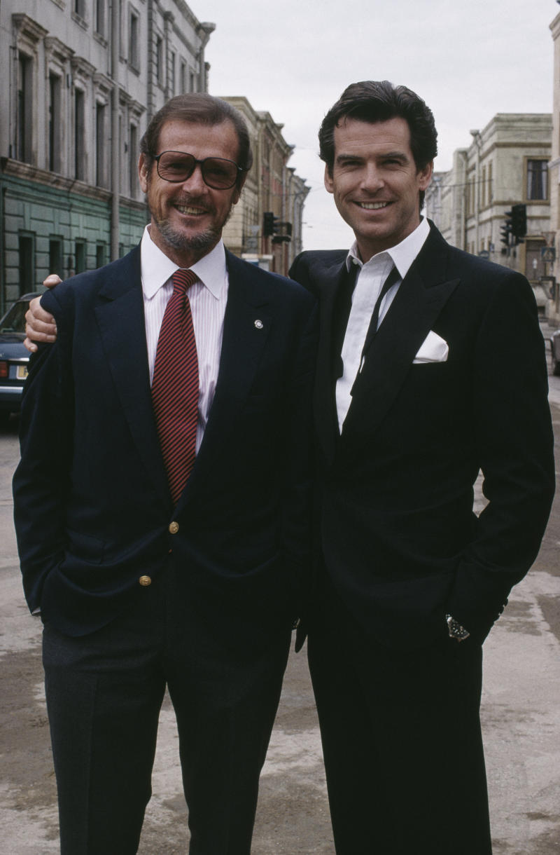 Irish actor Pierce Brosnan poses with Roger Moore, a former incarnation of superspy James Bond, on the set of the film 'GoldenEye', 1995. (Photo by Keith Hamshere/Getty Images)