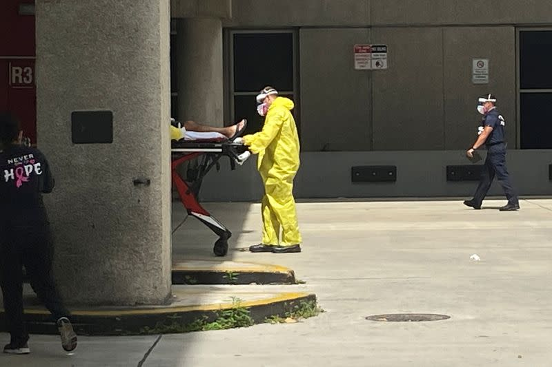 A patient is brought to Jackson Health Center by paramedics wearing protective clothing in Miami