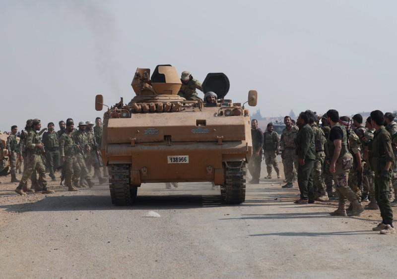 Turkey-backed Syrian rebel fighters gather as a military vehicle advances near the border town of Tal Abyad