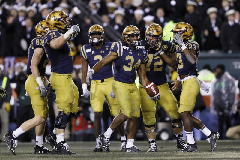Navy's Jamale Carothers (34) celebrates with teammates after scoring a touchdown during the second half of an NCAA college football game against Army, Saturday, Dec. 14, 2019, in Philadelphia. (AP Photo/Matt Slocum)