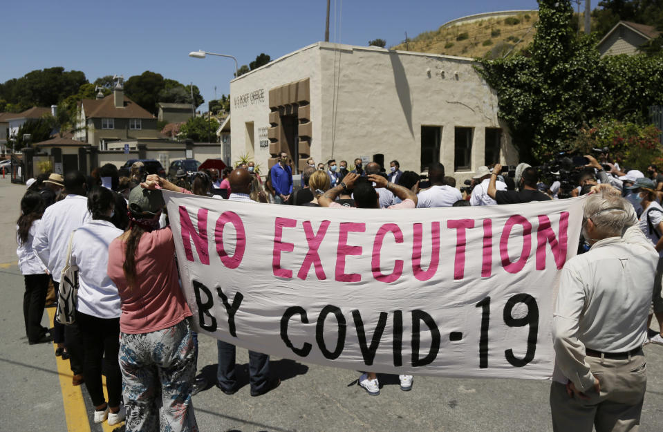 FILE - In this July 9, 2020, file photo, people hold up a banner while listening to a news conference outside San Quentin State Prison in San Quentin, Calif. One in five state and federal prisoners in the United States has tested positive for the coronavirus, a rate more than four times higher than the general population. In some states, more than half of prisoners have been infected, according to data collected by The Associated Press and The Marshall Project. (AP Photo/Eric Risberg, File)