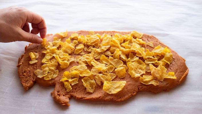 Photo of cornflakes laid out on the peanut butter and candy corn mixture. They're shingled in one layer.