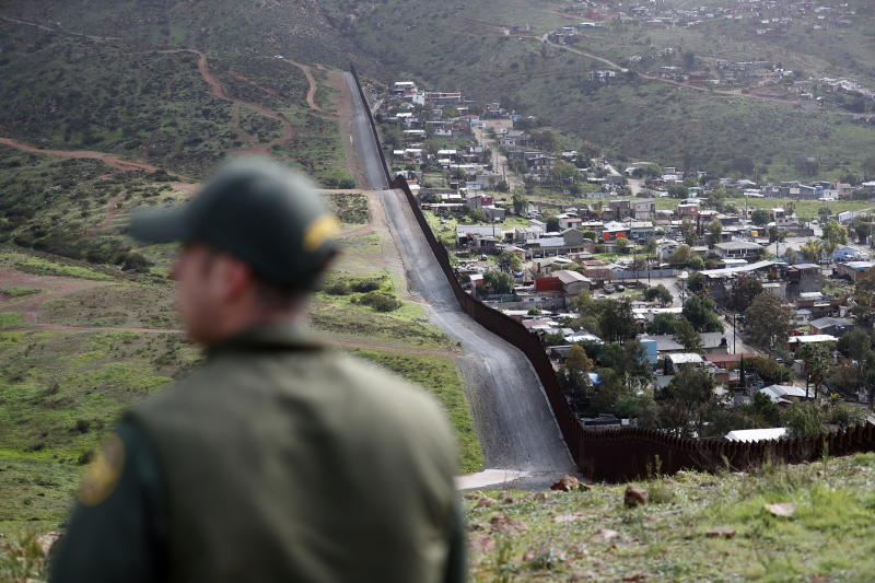 FILE - In this Feb. 5, 2019, file photo, Border Patrol agent Vincent Pirro looks on near a border wall that separates the cities of Tijuana, Mexico, and San Diego, in San Diego. Hundreds of thousands of people have been arriving at the border in recent months, many of them families fleeing violence and poverty in Central America. Once they reach the border, they can take different paths to try to get into the U.S. (AP Photo/Gregory Bull, File)