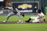 Houston Astros' Jose Altuve (27) slides safely into second base as Chicago White Sox second baseman Danny Mendick reaches for the throw from third baseman Yoan Moncada during the first inning of a baseball game Thursday, June 17, 2021, in Houston. Moncada was charged with a throwing error on the play. (AP Photo/David J. Phillip)