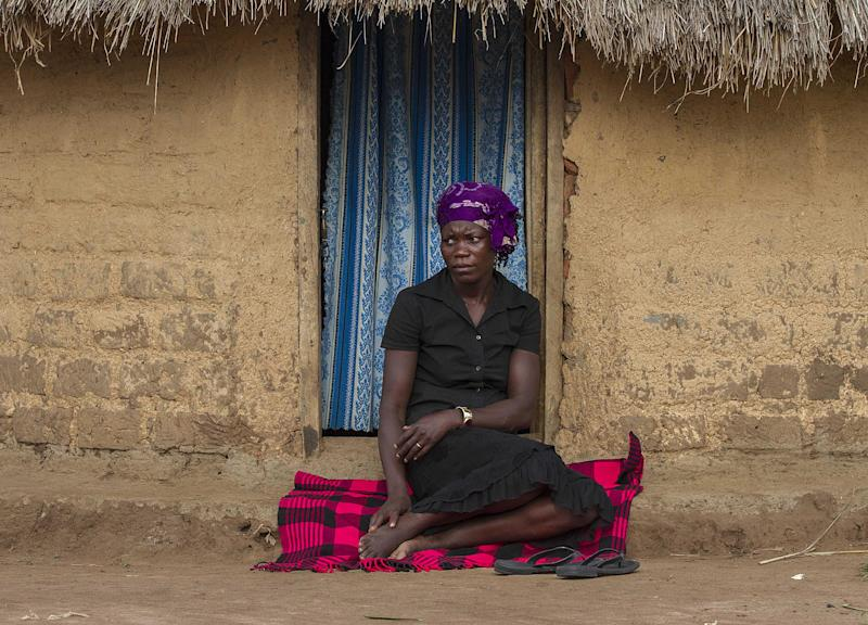 Janet Akiding, a victim of domestic violence, sits at the doorway of her father's homestead on September 25, 2014 in Uganda's Bukedea district after she ran away from her matrimonial home where she was battered by her husband (AFP Photo/Isaac Kasamani)