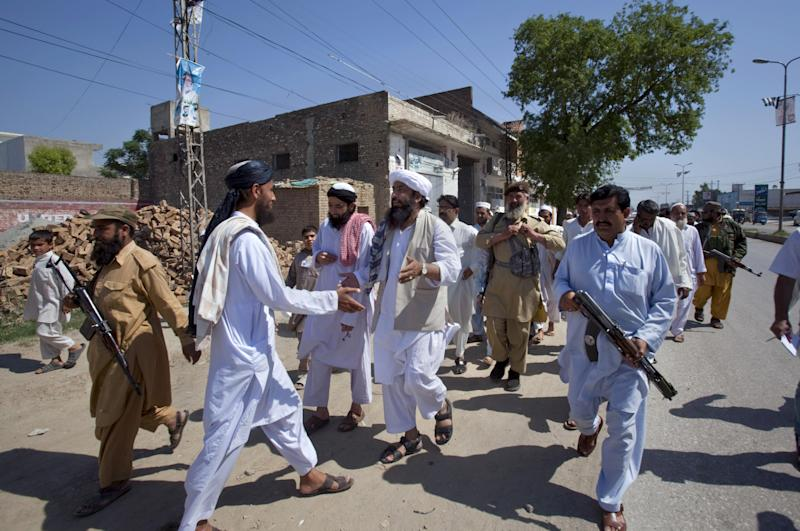 "In this Thursday, May 2, 2013 photo, Maulana Shujaul Mulk, center, pro-Taliban Jamiat-e-Ulema Islam (JUI-F), surround by guards as he greets a supporter during his election campaign at a road in Mardan, Pakistan. Mulk is among several Pakistani Islamists and sectarian groups contesting for the country's upcoming parliamentary elections, which are divided and scattered though, they are still in a position to secure enough strength to play Pakistani establishment bid to ""hound"" the next frail government in influencing its decisions about the U.S. forces withdrawal from Afghanistan in 2014. (AP Photo/Anjum Naveed)"