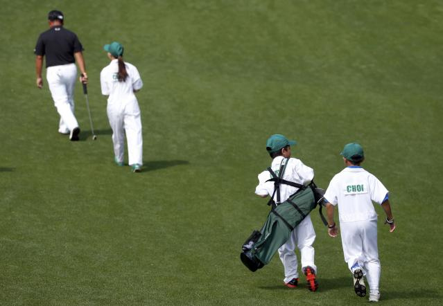 South Korean golfer K.J. Choi (L) leads his children down the first fairway during the Par 3 Contest ahead of the Masters golf tournament at the Augusta National Golf Club in Augusta, Georgia April 9, 2014. REUTERS/Mike Segar (UNITED STATES - Tags: SPORT GOLF)