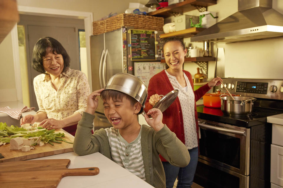 Family enjoy cooking together in a small kitchen