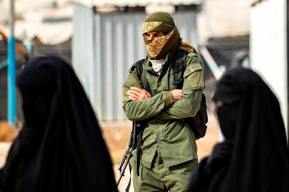A Kurdish fighter stands guard as Syrian women, suspected of being related to Isis, gather at the al-Hol camp (AFP/Getty)