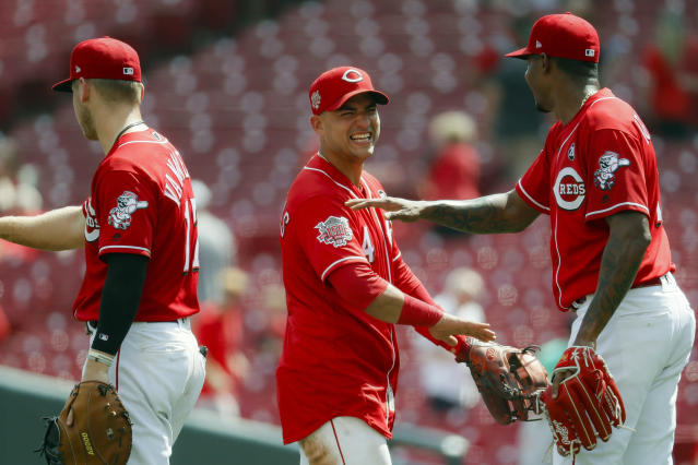 Cincinnati Reds shortstop Jose Iglesias, center, celebrates with relief pitcher Raisel Iglesias, right, after closing the ninth inning of a baseball game against the San Diego Padres, Wednesday, Aug. 21, 2019, in Cincinnati. (AP Photo/John Minchillo)
