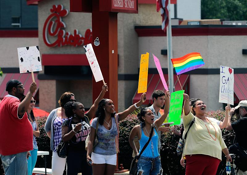 "Gay rights groups and others protest and hold a ""kiss-in"" outside the Decatur, Ga., Chick-fil-A restaurant Friday, Aug. 3, 2012 as a public response to a company official who was quoted as supporting the traditional family unit. About two dozen protesters gathered on the busy corner to voice their views. (AP Photo/David Tulis)"