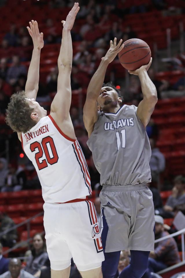 UC Davis guard Caleb Fuller (11) shoots as Utah forward Mikael Jantunen (20) defends during the first half of an NCAA college basketball game Friday, Nov. 29, 2019, in Salt Lake City. (AP Photo/Rick Bowmer)