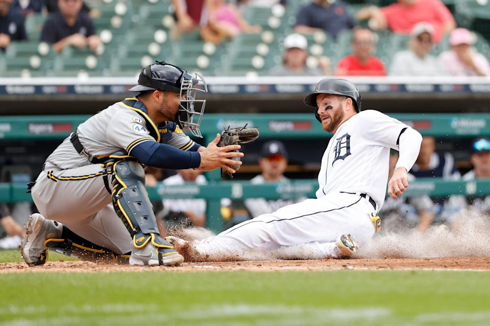 Detroit Tigers left fielder Robbie Grossman (8) slides in safe at home ahead of the throw to Milwaukee Brewers catcher Manny Pina (9) in the fourth inning at Comerica Park on Wednesday, Sept. 15, 2021.