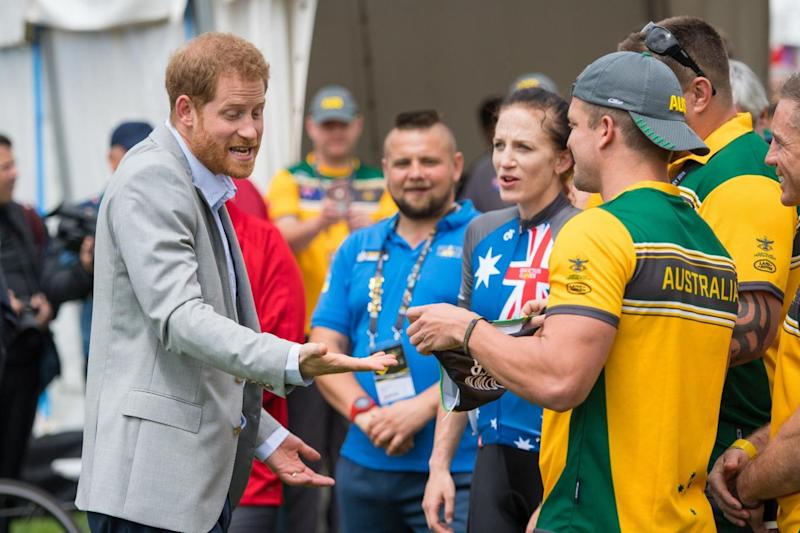 The Duke of Sussex reacts as Australian Invictus Games athlete Benjamin Yeomans asks him so sign a pair of swimming trunks (PA)