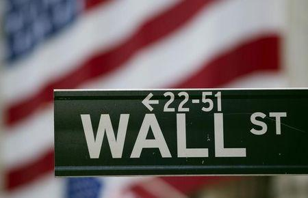 A Wall Street sign hangs on a signpost in front of the New York Stock Exchange