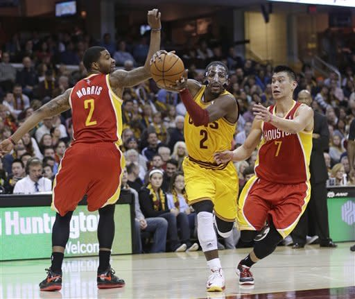 Cleveland Cavaliers' Kyrie Irving (2) drives between Houston Rockets' Marcus Morris (2) and Jeremy Lin (7) during the second quarter of an NBA basketball game Saturday, Jan. 5, 2013, in Cleveland. (AP Photo/Tony Dejak)