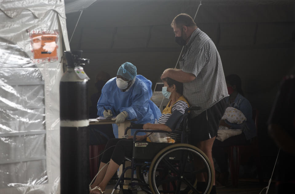 A patient is attended to at the Steve Biko Academic Hospital's outside parking area in Pretoria, South Africa, Monday, Jan. 11, 2021. As the numbers of new confirmed cases rise, South Africa's hospitals are exceeding capacity, according to health officials. (AP Photo/Denis Farrell)