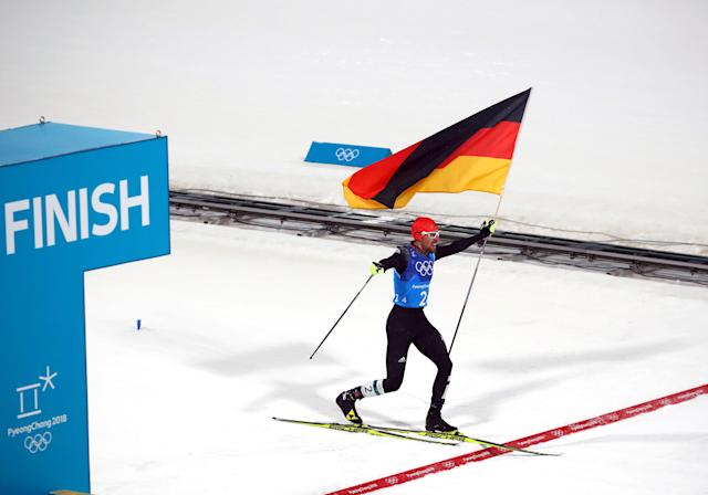 Nordic Combined Events - Pyeongchang 2018 Winter Olympics - Men's Team 4 x 5 km Final - Alpensia Cross-Country Skiing Centre - Pyeongchang, South Korea - February 22, 2018 - Johannes Rydzek of Germany waves the German flag as he crosses the finish line. REUTERS/Carlos Barria
