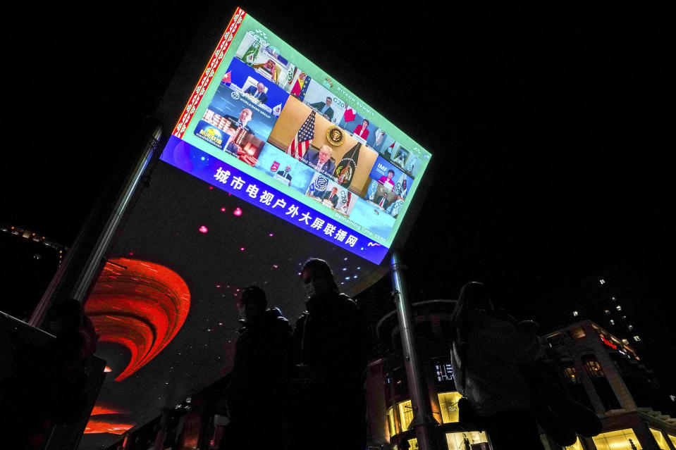 People wearing face masks to help curb the spread of the coronavirus walk by a giant TV screen broadcasting news of U.S. President Donald Trump, center, and other leaders participating in a virtual G20 summit, at a shopping mall in Beijing, Sunday, Nov. 22, 2020. The Group of 20 summit opened on Saturday with appeals by the world's most powerful leaders to collectively chart a way forward as the coronavirus pandemic overshadows this year's gathering, transforming it from in-person meetings to a virtual gathering of speeches and declarations. (AP Photo/Andy Wong)