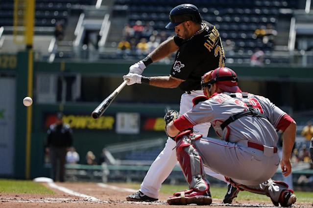 Pittsburgh Pirates' Pedro Alvarez (24) drives in a run with a single off Cincinnati Reds starting pitcher Tony Cingrani during the first inning of a baseball game in Pittsburgh Thursday, April 24, 2014. Catching is Reds' Devin Mesoraco (39). (AP Photo/Gene J. Puskar)