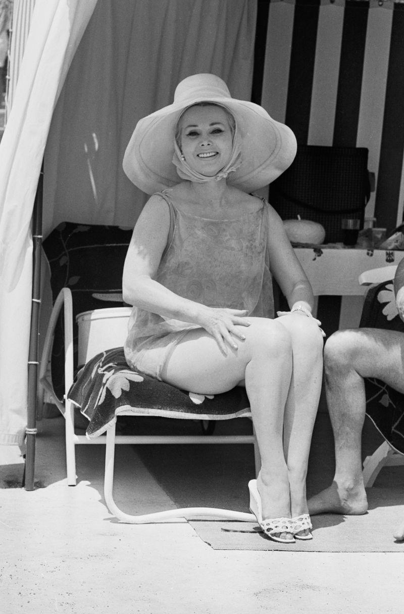 <p>Zsa Zsa Gabor hides from the sun with a wide-brimmed hat, while she relaxes in a cabana in the South of France in 1964.</p>