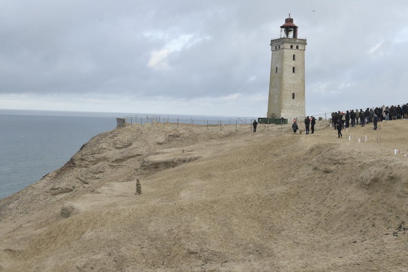 People look on as the lighthouse in Rubjerg Knude is being moved away from the coastline (Picture: AFP/Getty)