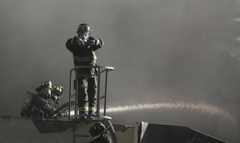 Firefighters work to put out flames at a building that caught on fire amid an anti-government protest where police were firing tear gas and water cannons in Santiago, Chile, Friday, Dec. 27, 2019. Chile has been roiled by continuing and sometimes violent street protests since Oct. 18, when a student protest over a modest increase in subway fares turned into a much larger and broader movement with a long list of demands that largely focus on inequality. (AP Photo/Fernando Llano)
