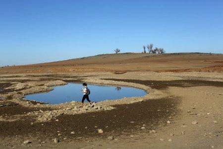 FILE PHOTO - A visitor walks near the receding waters at Folsom Lake, which is 17 percent of its capacity, in Folsom, California January 22, 2014. REUTERS/Robert Galbraith/File Photo