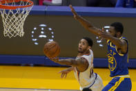 Phoenix Suns guard Cameron Payne, left, shoots against Golden State Warriors forward Andrew Wiggins (22) during the first half of an NBA basketball game in San Francisco, Tuesday, May 11, 2021. (AP Photo/Jeff Chiu)
