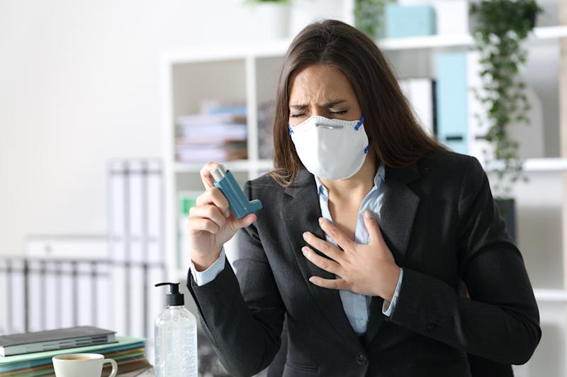 Executive woman wearing protective mask with asthma attack holding inhaler touching chest at the office