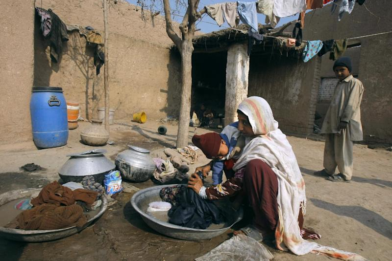 In this Jan. 30, 2014 photo, Pakistani Samia Gul, holds her 11-month-old daughter, Shaista, while doing her laundry at her home in Peshawar, Pakistan. Then the polio virus struck Shaista and she was no longer able to stand, her legs buckling beneath her weight. Her mother cries a lot and wonders what will become of her daughter, already at a disadvantage in Pakistan's male-dominated society, where a woman's value is often measured by the quality of her husband. (AP Photo/Mohammad Sajjad)